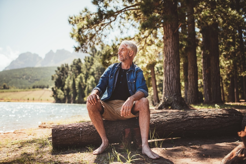 Portrait of senior man sitting on a wooden log and looking at the lake. Mature man camping by a lake.